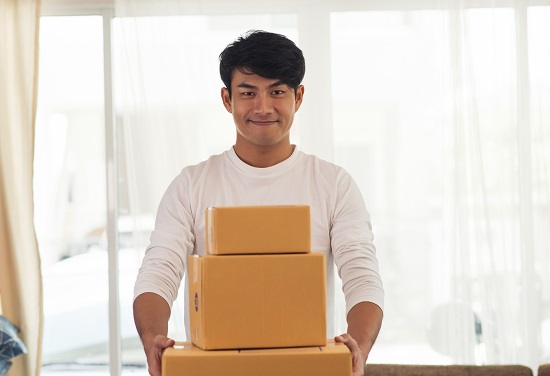 Young smiling logistic delivery man holding the box