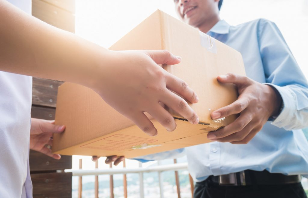 Hand of asia woman are receive a box from delivery man in delivery service concept.